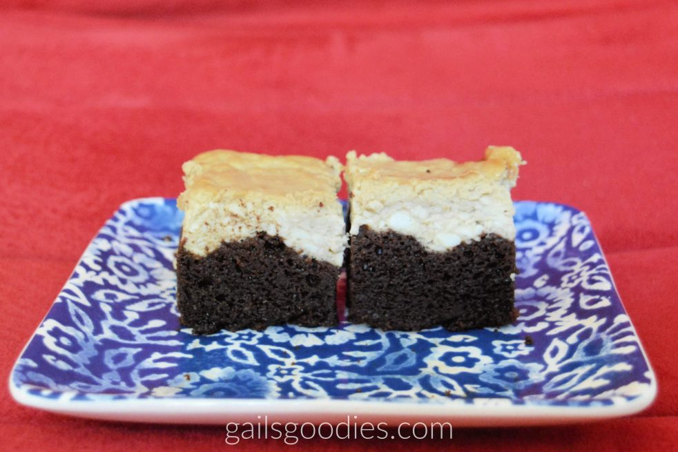 Two gluten free mocha cheesecake brownies sit on a blue and white paisley plate. The dark chocolate brownies contrast sharply with the pale brown mocha cheesecake on top.