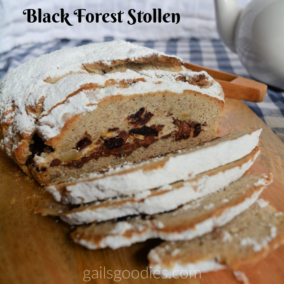 A black forest stollen loaf with several slices removed sits on a wooden board. The round loaf is dusted generously with powdered sugar. The front of the loaf is sliced.and there is a long band of cherries, chocolate and candied citrus peel in the middle. The tan colored bread is speckled with spices.