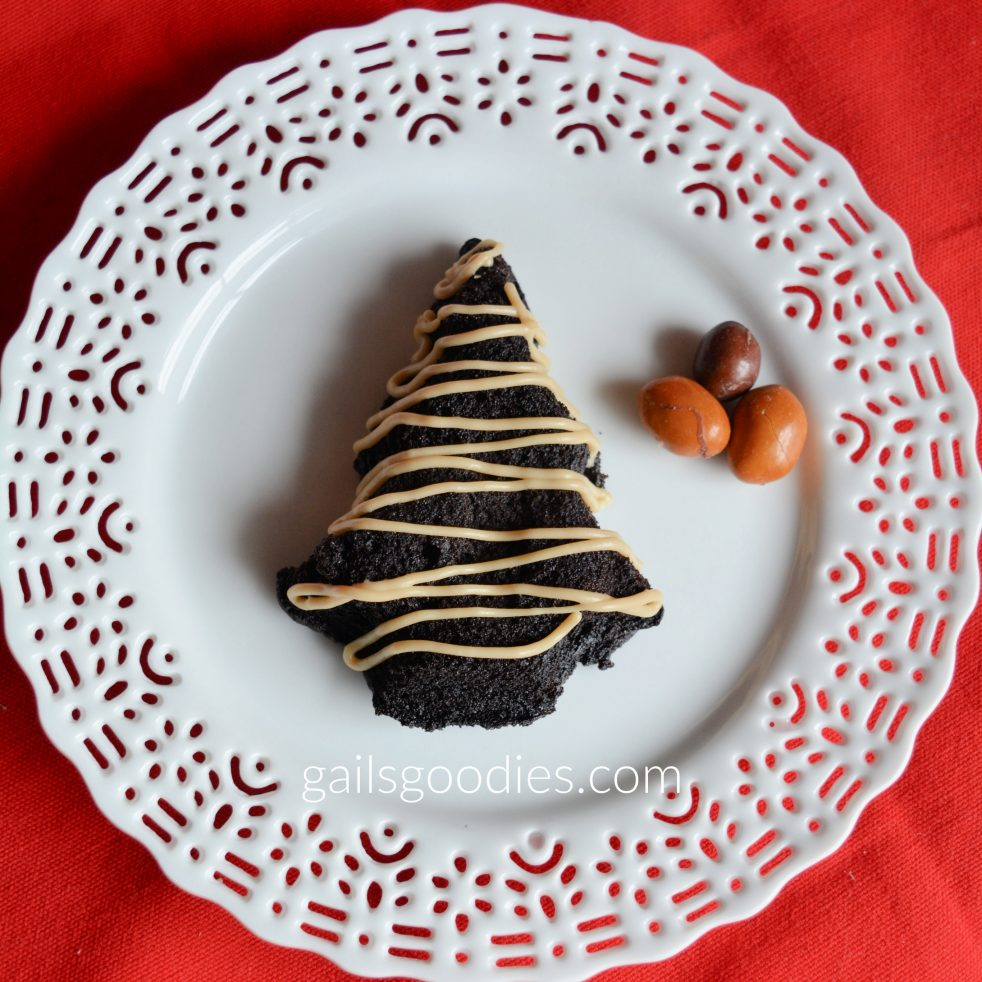 A single dark chocolate Christmas tree cake sits on a white plate with lacey edges. The tree is drizzled with White Chocolate Kahlua ganache. There are three coffee peanut M&Ms on the plate to the right of the tree.