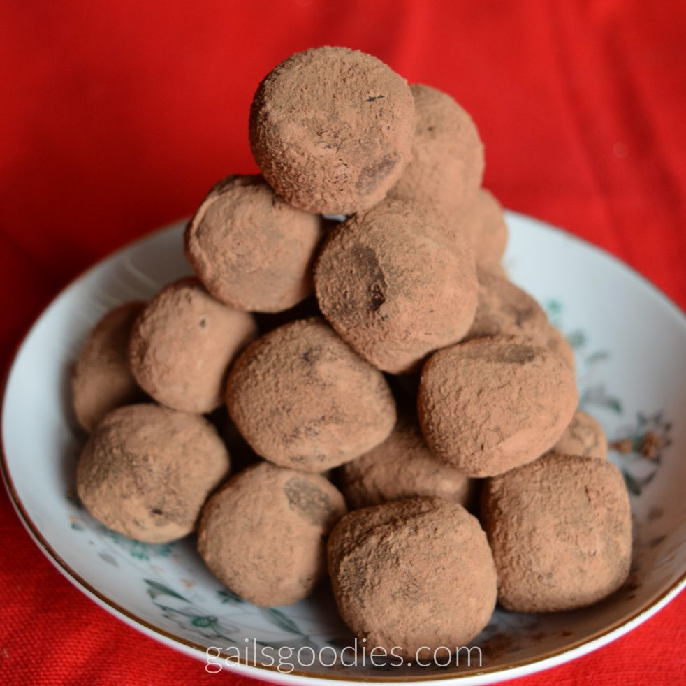 A small dessert plate with a large pyramid of dark chocolate truffles. The cocoa powder coating makes them look a little fuzzy and hides the dark chocolate ganache beneath.