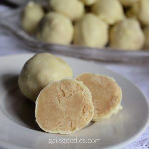 Two white chocolate chai truffles are on a white plate. The one on th eback left is still whole and is a pale yellow sphere. The one on the right front has been cut in half revealing a tea latte-colored center coated with a thin layer of white chocolate on the outside. There is a glass serving dish behind the plate with more truffles stacked on it.