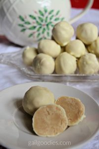 Two white chocolate chai truffles are on a white plate. The one on the back left is still whole and is a pale yellow sphere. The one on the right front has been cut in half. The two halves face forward revealing a tea latte-colored center coated with a thin layer of white chocolate on the outside. Behind the plate there is a glass serving dish with more truffles stacked in a pyramidon. There is a white teapot decorated with holly and berries behind the plate of truffles.