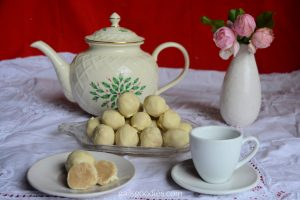 This photo shows a tea time table with a white lace table cloth and a red background. At the back left of the photo there is a white teapot decorated with holly and berries. To the right of the teapot is a bud vase with three small pink roses. In front of the teapot and vase in the center of the photo is a serving tray with white chocolate truffles stacked in a small pyramid. At the bottom right is a white tea cup and saucer. At the bottom left is a small white plate with two white chocolate truffles. The white truffle chocolate in the rear is whole while the one in front is sliced in half. The two halves are turned forward revealing the tea-latte colored truffle surrounded by a thin layer of pale yellow white chocolate.