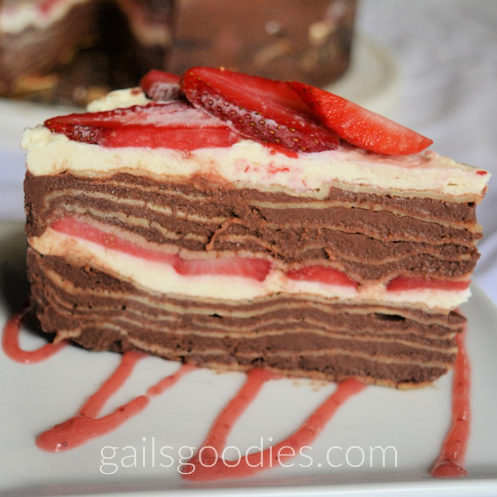 A slice of chocolate strawberry crepe cake sits on a white plate so that the side faces the front of the photo. There are six crepes with chocolate cream patissiere in between. Then there is a layer of whipped cream and strawberries followed by another 6 layers of crepes and chocolat cream patissiere. The top of the cake is covered with whipped cream and sliced strawberries.