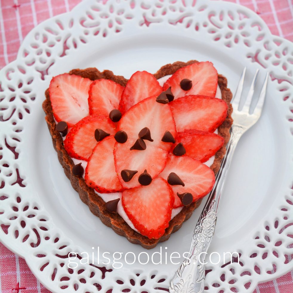 A single strawberry marshmallow tart on a white dessert plate with lacey edges. The heart-shaped tart is topped with fresh strawberries and sprinkled with mini chocolate chips. A little of the pink strawberry marshmallow mousse peeks out between the fresh strawberries and the chocolate crust. There is a fork on the plate to the right of the tart.