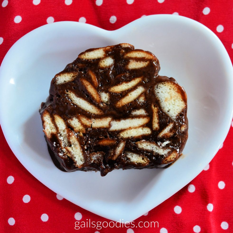 A slice of mosaiko on a white heart-shaped plate. The slice is viewed from above. The bottom and sides of the slice a flat and the top is rounded (like a slice of bread). crescent-shaped slivers of cream colored cookies are scattered generously in the moist chocolate base.