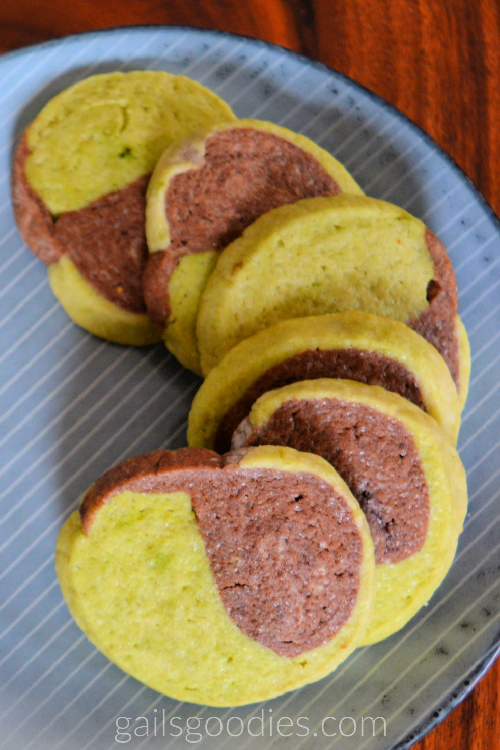 Six green tea chocolate sugar cookies are arranged in a curve along the right side of a grey plate. The round cookies are lime green on one side and milk chocolate on the other.