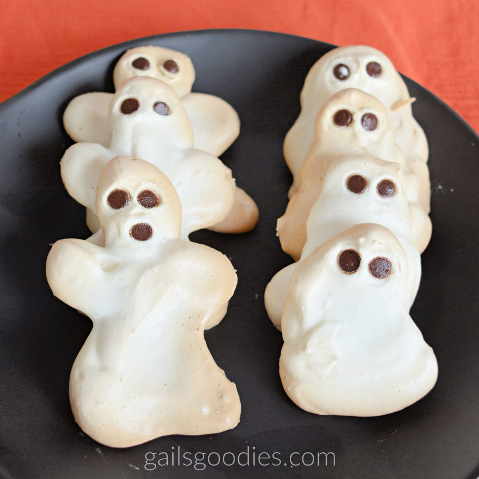 Two rows of ghost meringues arranged vertically on a black plate. The row on the left has three ghost meringues. Each meringue has two arms and a free form bottom. The meringues have two mini chocolate chips for eyes and one mini chocolate chip for a mouth. The row on the right has four meringues that lack arms. The shape of these ghosts is more like a sheet over someone's head. The simpler meringues on the right only have two mini chocolate chip eyes and no mouth.