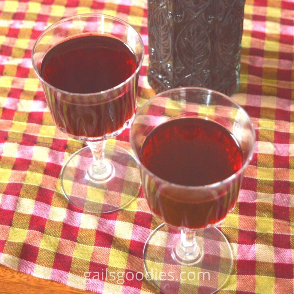 Two glasses and a bottle of blackberry liqueur sit on a checked cloth. The view is from about 60 degrees above the table. One wine glass is in the lower right corner of the photo and the other is in the upper left. The decorative bottle filled with blackberry liqueur is directly behind the glass on the right. The blackberry liqueur in the glasses is a reddish purple. The liqueur in the bottle appears a dark red wine color.