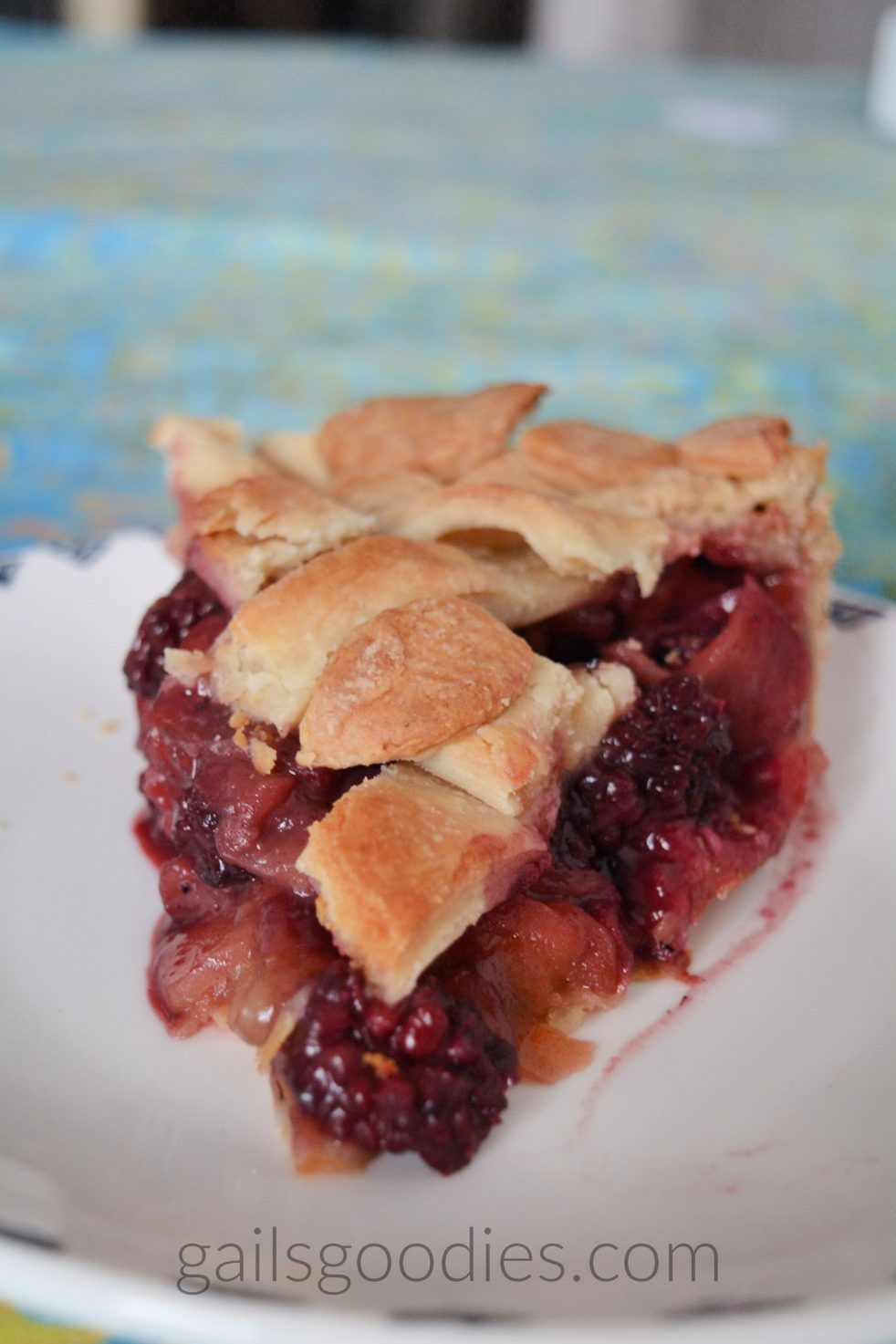 A slice of blackberry apple pie pointed towards the front of the photo. There is a blackberry at the point of the slice and bits of apple and blackberry line both sides. The pie is topped with a golden lattice top.