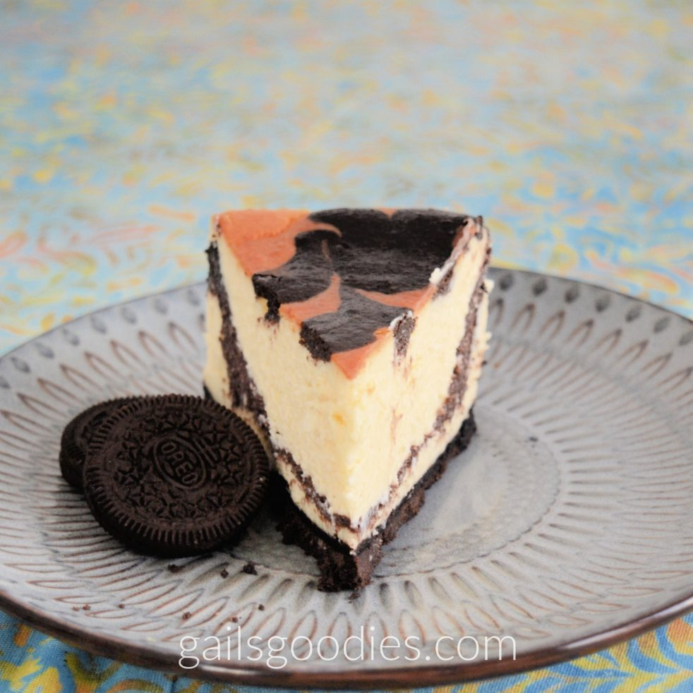A slice of oreo swirled cheesecake on a grey plate. The golden cheesecake points directly at the viewer and a dark chocolate band curves from the top of the back of the slice to near the bottom of the front. The cheesecake has a golden brown top with dark brown swirls and the cheesecake has a black chocolate crust. There are two oreos to the left of the slice.