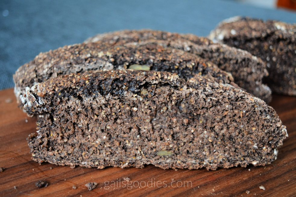 Four slices of pumpernickel bread are arranged vertically on a wooden board so the cut side faces the viewer. The slices are narrow and oblong. The bread is dark chocolate brown and has a grainy texture.