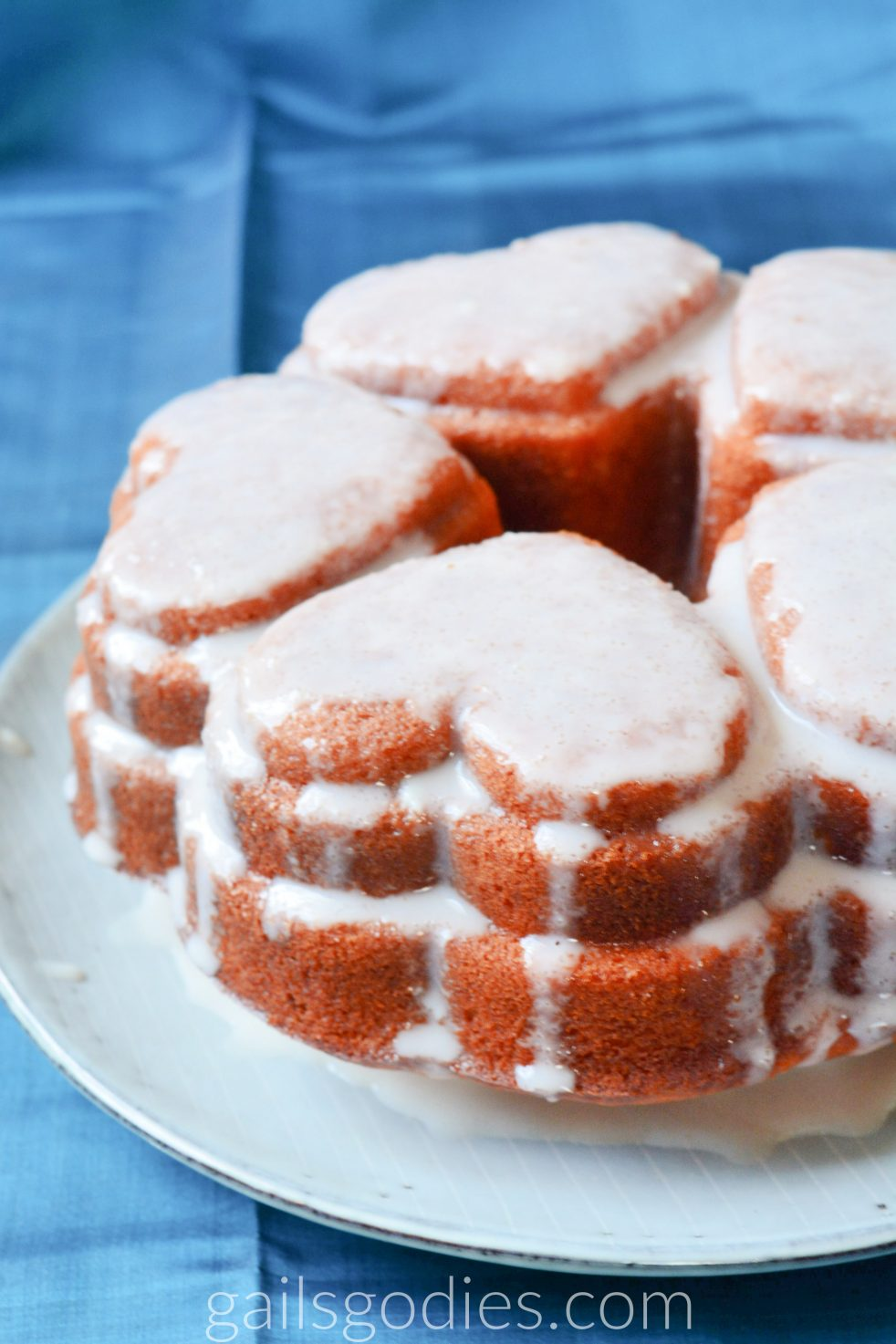 This is the left side of a champagne bundt cake. The bundt cake is five hearts. Three hearts are fully visible and the other two are only partially visible. The cake is glazed with a light pink glaze that drizzles down the sides.