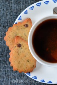 Two hedgehog shaped cookies are on a saucer next to a tea cup. Only half the tea cup is visible and it is filled with dark brown tea. The top cookies is pointed towards the cop of the photo. The second cookie is about halfway under the first one and is also pointed towards the top of the photo