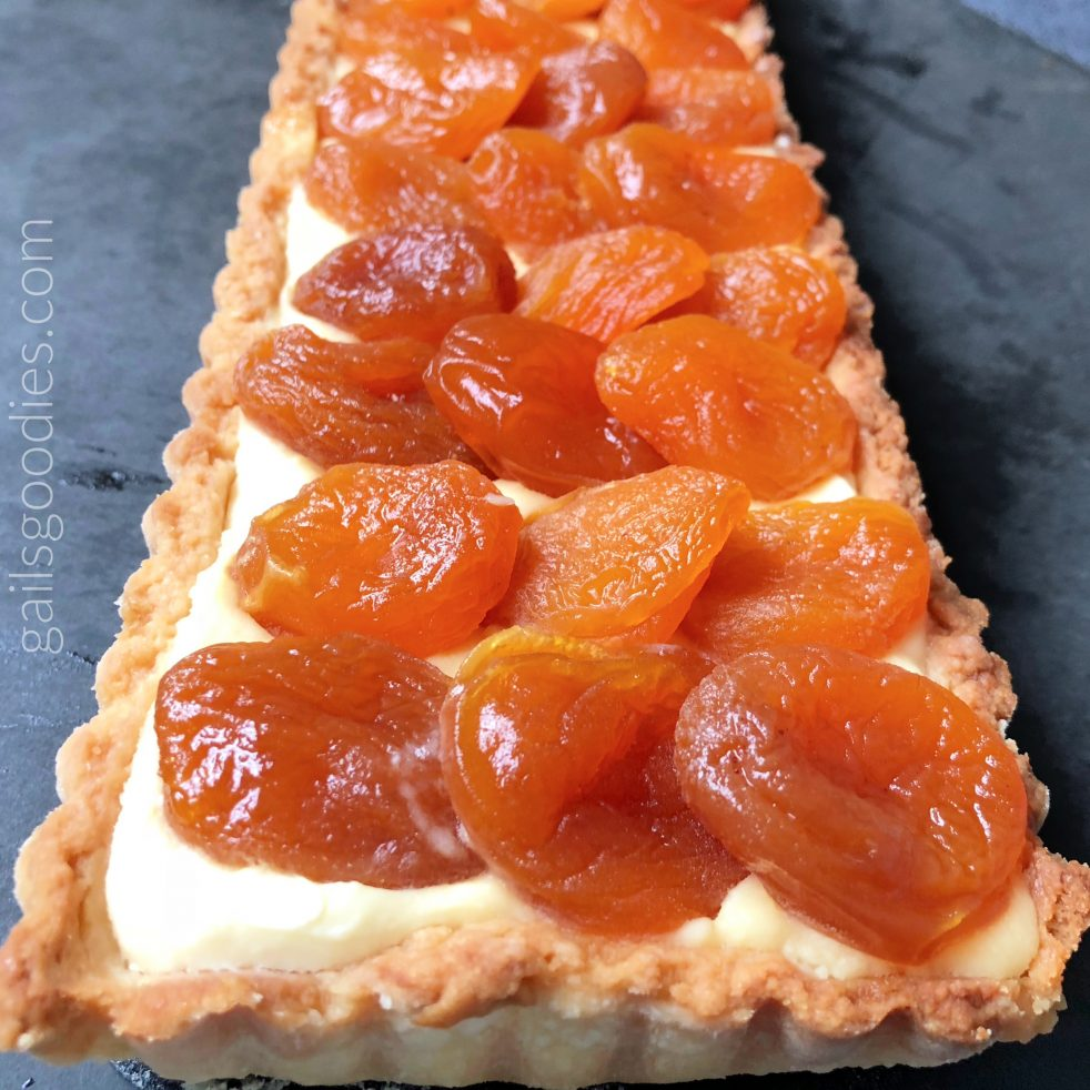 The front end of an Apricot mascarpone tart. The buttery crust of the rectangular tart is filled with creamy mascarpone and topped with rows of mulled apricots. Each row has 3 apricots.