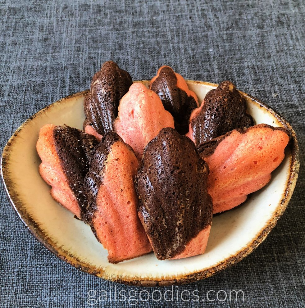 Eight chocolate cherry madeleines are in a white bowl with brown edges. each madeleine has dark chocolate areas and pink areas. The madeleines are shaped like fleur de lis.