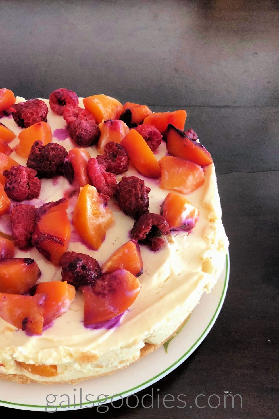 The right side of a peach melba cheesecake . The creamy filling is dotted with peaches. The top is covered in peaches and raspberries.