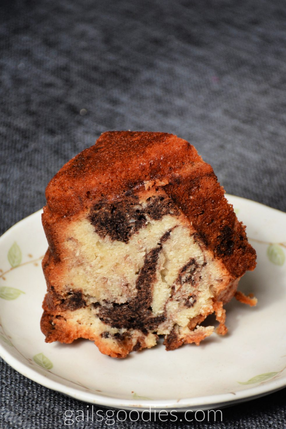 This is a slice of coconut marble bundt cake with no ganache. The cut side is facing the front of the photo. There are several chocolate swirls at the bottom and top of the slice.
