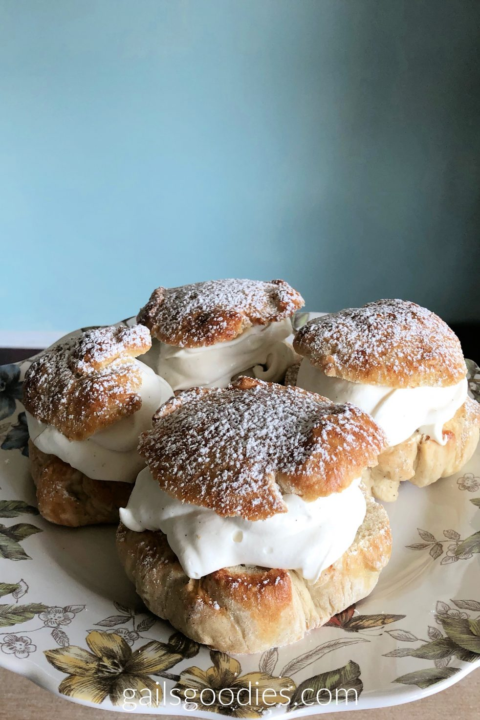 Four Almond Semlor are arranged on a plate with a floral border. The golden tops of the semlor sit on a generous helping of whipped cream. They are dusted with powdered sugar.