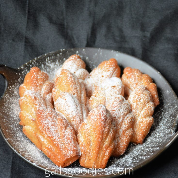Golden brown ginger madeleines are arranged in four rows on a round black plate. There are two feather shaped madeleines in the front row. There are three madeleines behind the two in the front, then four madeleines in the third row and three in the fourth row. The madeleines are dusted with powdered sugar.