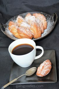 There is a square black plate at the bottom of the photo. On the upper left side of the plate sits a white mug of coffee. A silver spoon is on the plate just below the mug of coffee and a golden brown madeleine is in the lower right corner of the plate. Behind the plate at the top of the photo sits a round plate filled with golden madeleines. The madeleines are dusted with powdered sugar.