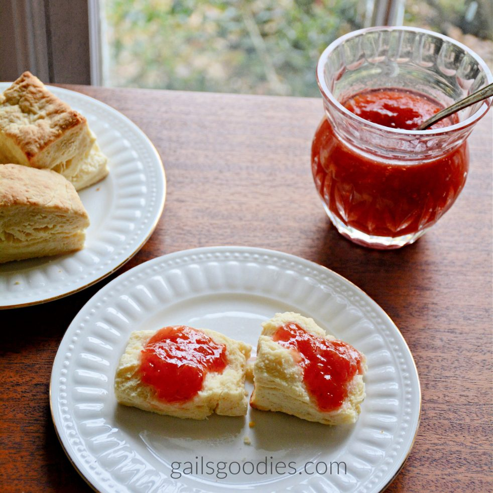 There is a white plate with a biscuit that has been split open. The two halves of the biscuit are topped with ruby red marmalade. An open glass serving jar of marmalade is in the upper right corner and a pate with 2 more biscuits is in the upper left corner of the photo.