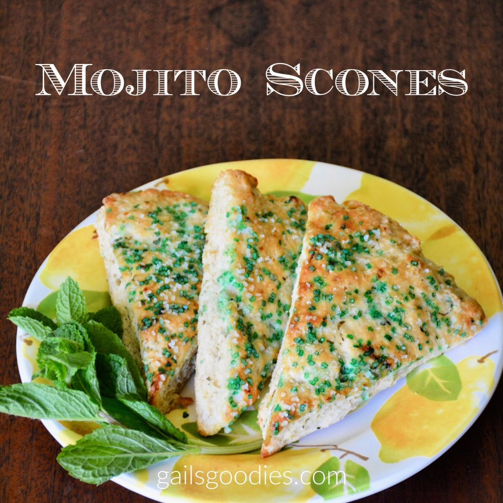 Three Mojito Scones sit on a white plate decorated with yellos lemons.The triangular scones are arranged with their points towards the front of th photo. They overlap each other so that the one on the right is the only one fully visible. There is a generous sprig og mint curved around the left side of the plate. The words Mojito Scones are at the top of the photo.