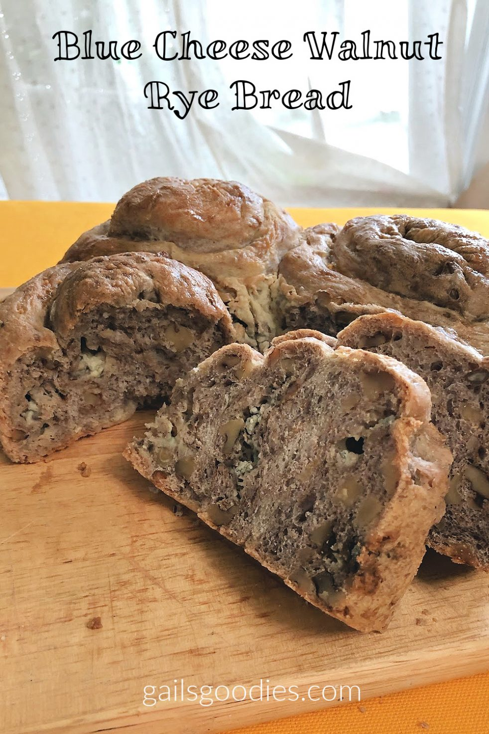 A loaf of blue cheese walnut rye bread sits on a pale brown wooden board. The Bread has been sliced and two slices are propped up against the cut loaf. The slice in the foreground had three clear pockets of blue cheese and the slice is vertically streaked with lighter blue cheese and darker rye. The sliced section of the loaf faces the viewer and has two pockets of blue cheese along with striations of rye and lighter bread. Two of the rolled knots in the loaf are visible behind the slices.