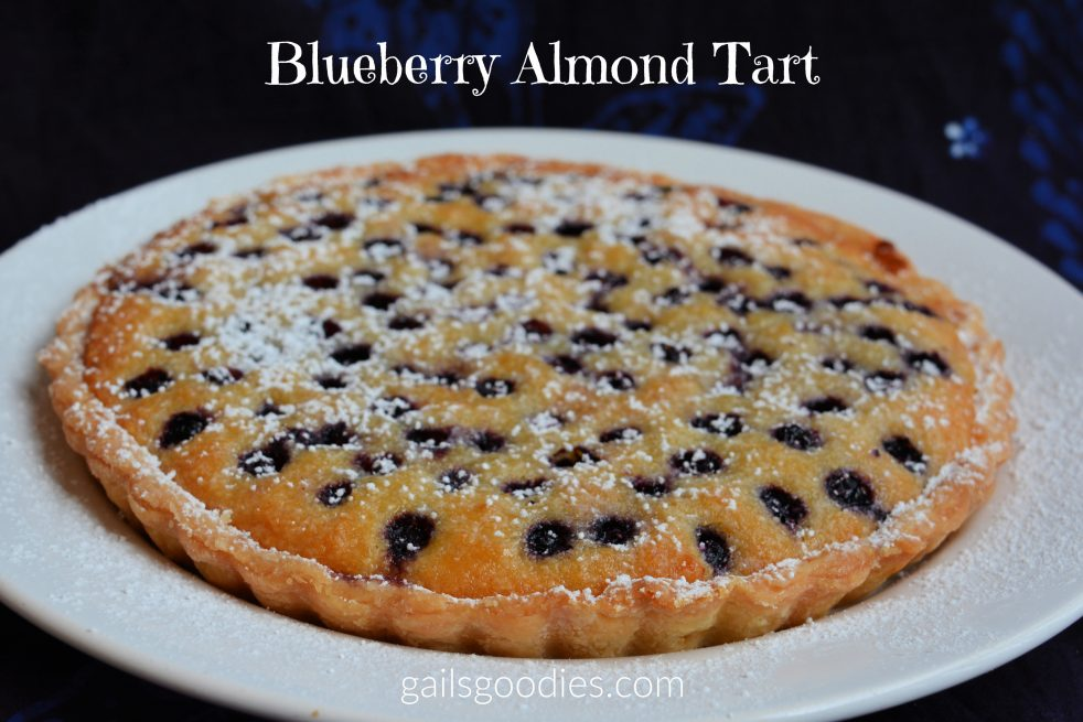 "A whole blueberry almond tart sits on a white plate. The crust is golden brown and the almond filling is golden brown at the edges fading to yellow in the middle. The tart is dotted with blueberries and dusted with powdered sugar. The plate sits on a navy tablecloth and the words ""Blueberry Almond Tart"" are at the top of the photo."