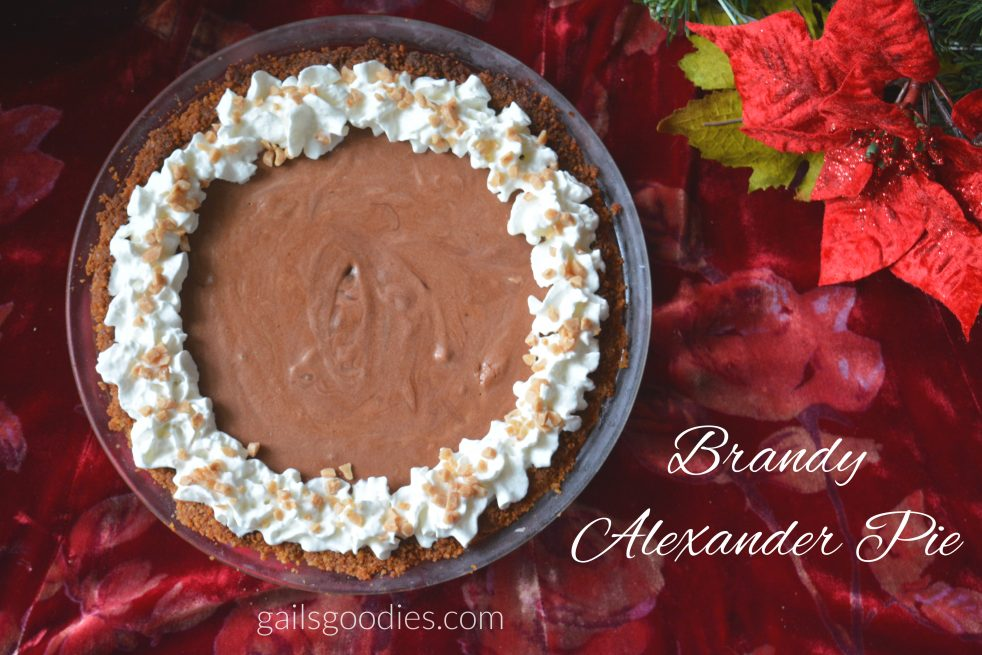 "A brandy alexander pie viewed from above. A creamy chocolate filling surrounded by dollops of whipped cream sprinkled with small pieces of toffee. The pie sits on a red velvet cloth and there is a pointsettia in the upper right corner. The words ""brandy alexander pie"" are in the lower right corner of the photo."
