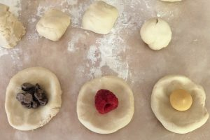 This photo shows the assembly of the brioche donuts. There are three discs of donut dough along the bottom of the photograph. The bottom left disk has a small pile of chocolate chips in the center. The middle disc has a raspberry in the center and the disc on the right two lemon discs in the center. There are four balls of brioche dough in a row above the three disks and there is some flour on the pink laminate between the dough balls and the disks.