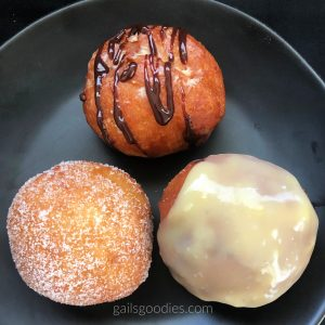 Three brioche donuts arranged in a triangle on a black plate. The top donut is fried golden brown with a drizzle of dark chocolate on top. The bottom left donut is a paler golden brown and is coated with sugar. The bottom right donut is covered with pale yellow ganache.