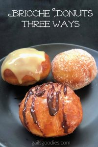 "Three golden brown brioche donuts are arranged on a black plate. The donut in the front is drizzled with dark chocolate ganache. The donut in the upper left is covered in a pale yellow ganache that drips down the sides. The donut in the upper right is covered in granulated sugar. The words ""Brioche Donuts Three Ways"" are at the top of the photo."