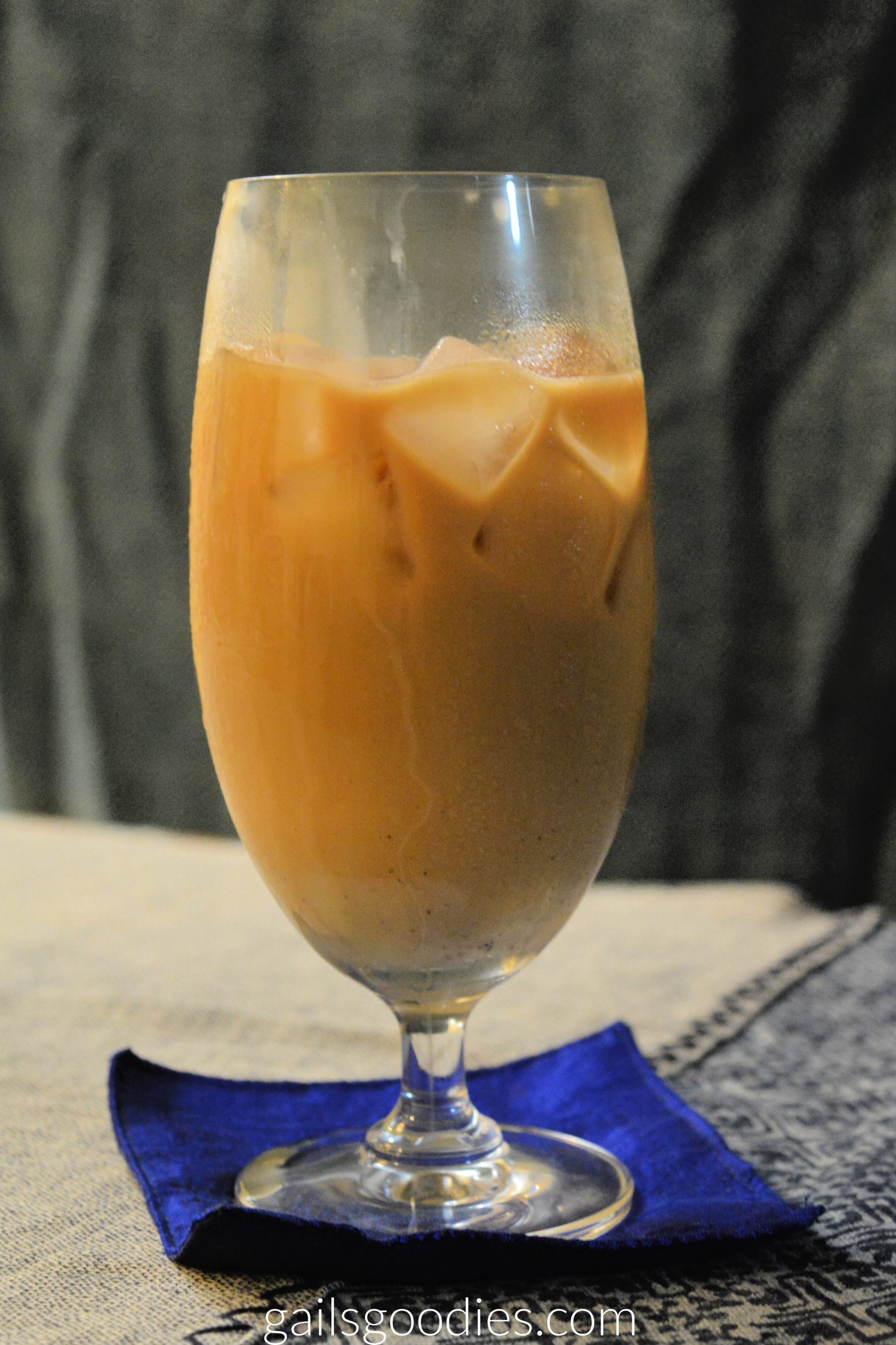 a tall stemmed glass of creamy iced coffee. There is a little layer of sweetened condensed milk at the bottom and caramel colored coffee mixture on top. Several ice-cubes are floating at the top.