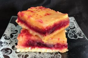 Two Cranberry Lemon Bars are stacked on top of each other on an etched glass plate. The bottom bar is parallel with the plate. The bar on top is at a 45 degree angle. The cream colored crust stands in sharp contrast to the bright red cranberry layer and bright yellow lemon layer. There are some spots of red on the top of the lemon layer. The background is black.