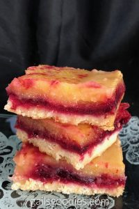 A stack of three cranberry lemon bars on an etched glass plate. The bottom and top layers are parallel with the bottom of the photo. The middle layer is at a 45 degree angle. The crust is a cream color and contrasts with eht bright red cranberry layer. The yellow lemon layer is a botu as thick as the cranberry layer.