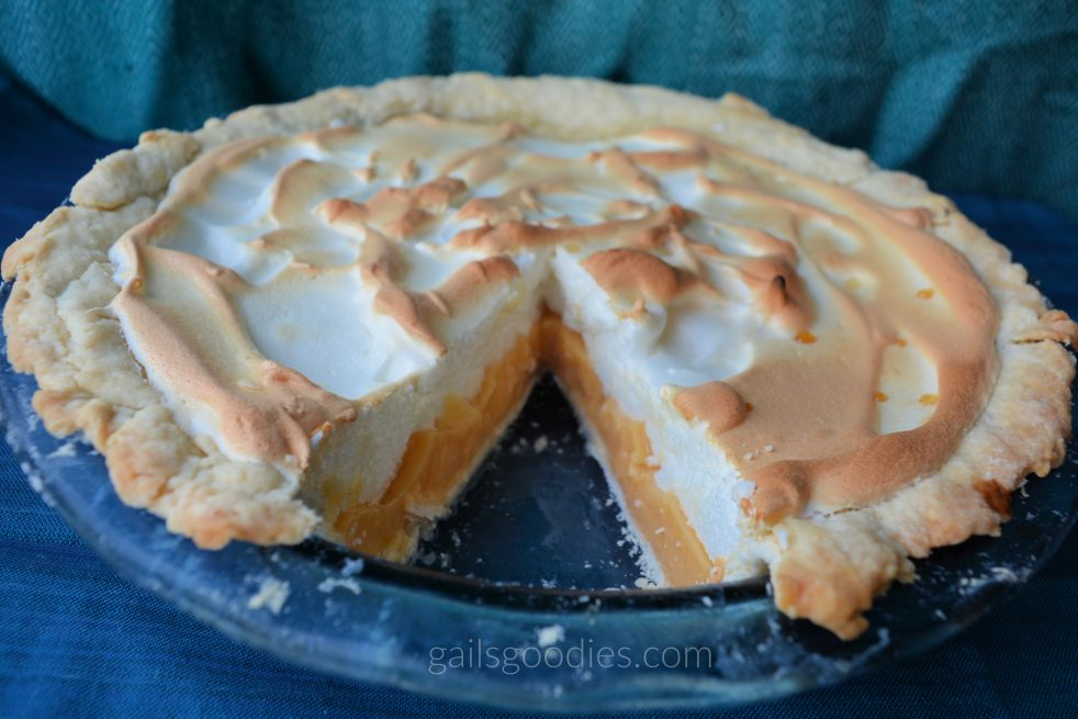 Grapefruit mering pie in a blue pie plate. The background is teal and blue. There is a slice removed from the front so the peach colored filling is visible under the fluffy meringue topping.
