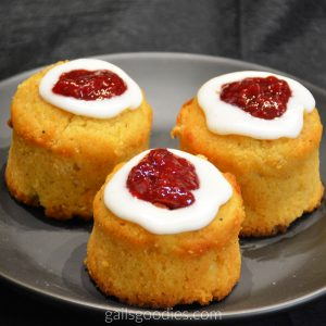 Three golden runberg cakes sit on a black plate. The top of each cake is ringed with white icing. Inside the ring of white icing dollops of crimson red raspberry jam mound slightly higher than the cakes.