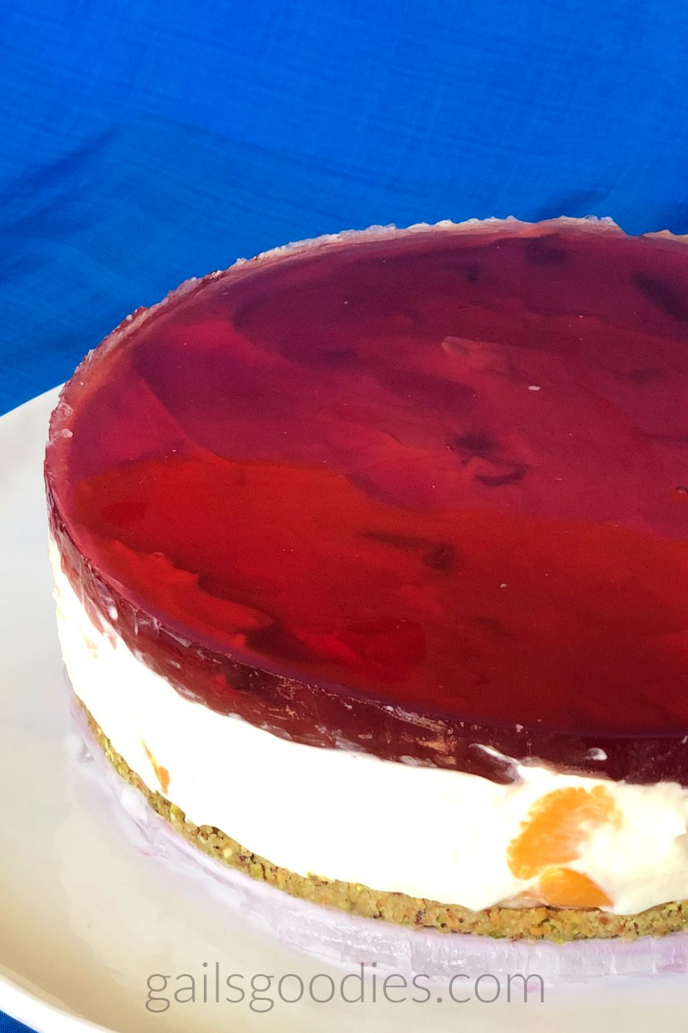 This is a view of the left half of a blackberry mead peach cheesecake. The cheesecake sits on a white plate and is viewed from above at about a 45 degree angle. Peach pieces and ripples in the creamy cheesecake below can be seen through the transparent raspberry red gelatin layer on top of the cake. Below the half inch thick gelatin layer there is a cream colored cheesecake. Peach chunks dot the creamy cheesecake in front and on the left side. The cookie crust at the bottom is tinged slightly green from the pistachios.