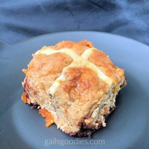 A single hot cross bun sits on a black plate.  The bun is square and one end points towards the front of the plate so the cross looks like an x.  The white cross is tinged a little orange but contrasts with the golden crust of the bun. There is a small piece of candied orange peel at the bottom left side of the bun and there are several more small pieces of candied orange peel along the right side of the bun. There are also several chocolate spots at the bottom of the bun.