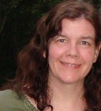 A white woman with long, wavy, brown hair and green eyes. She is wearing an olive green shirt.