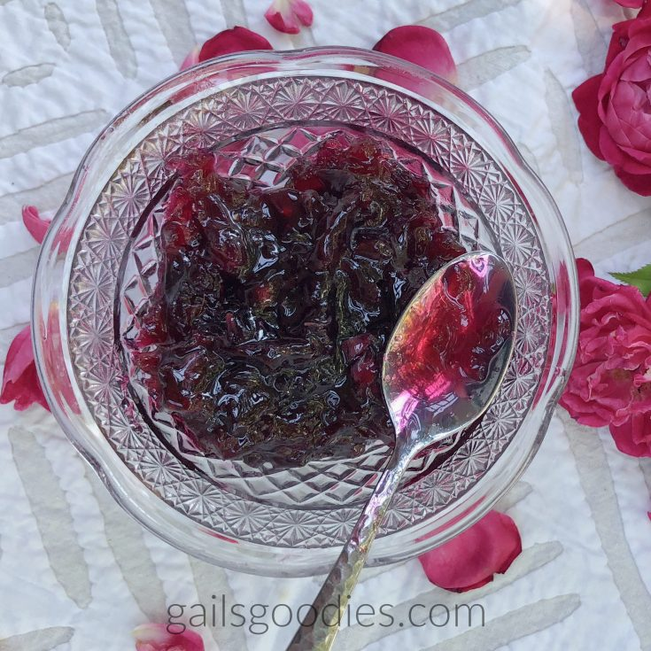This is a view from above of a cut glass bowl with rose jelly. The deep magenta rose jelly is textured with rose petals. There is a silver spoon on the right side of the container. Some of the jelly fills the bowl of the spoon. There are magenta roses on the white table cloth to the right of the bowl and magenta rose petals are scattered on the tablecloth around the glass bowl.