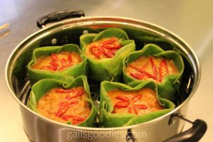 Five banana leaf bowls filled with orange fish amok.They are in a pan and each is decorated with slices of thai chili.