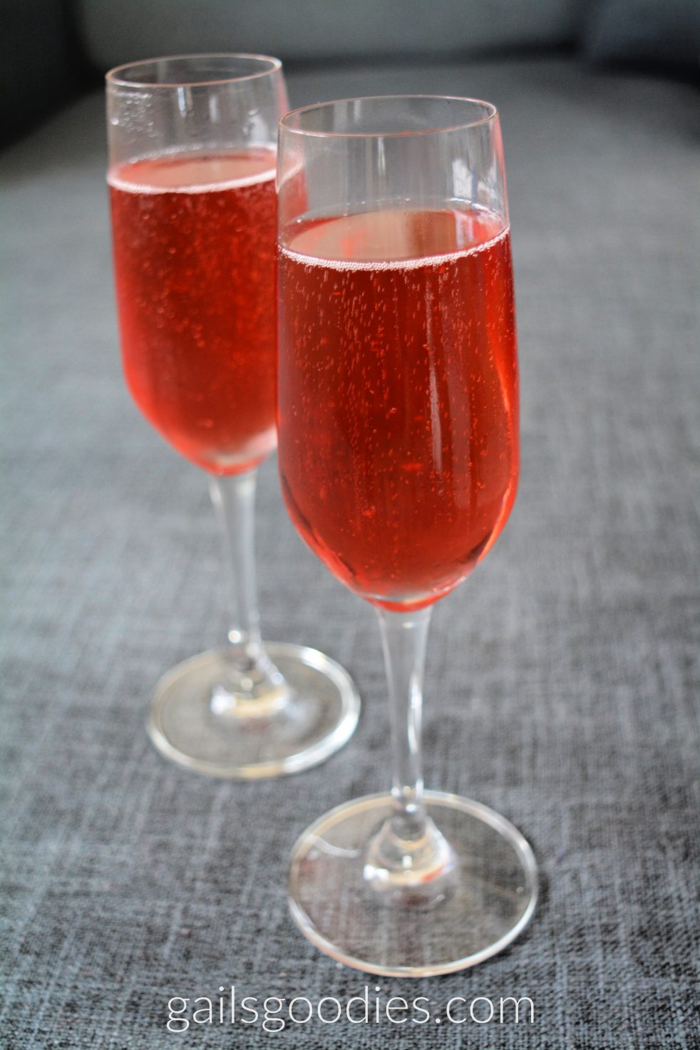 Two champagnes flute fille with clear cherry red liquid. One flute is just to the right of center at the front of the photo. The other is behind it and about 45 degrees to the left. Bubbles line the tops and are scattered on the sides of the liquid.