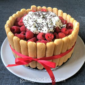 A whole charlotte sits on a white plate. Vertical lady finger cookies circle the entire outside of the cake. A red ribbon encircles the outside of the cake and is tied in a bow in the center. The top of the charlotte is covered in fresh raspberries. A large mound of whipped cream and chocolate sprinkles is in the very center of the charlotte.