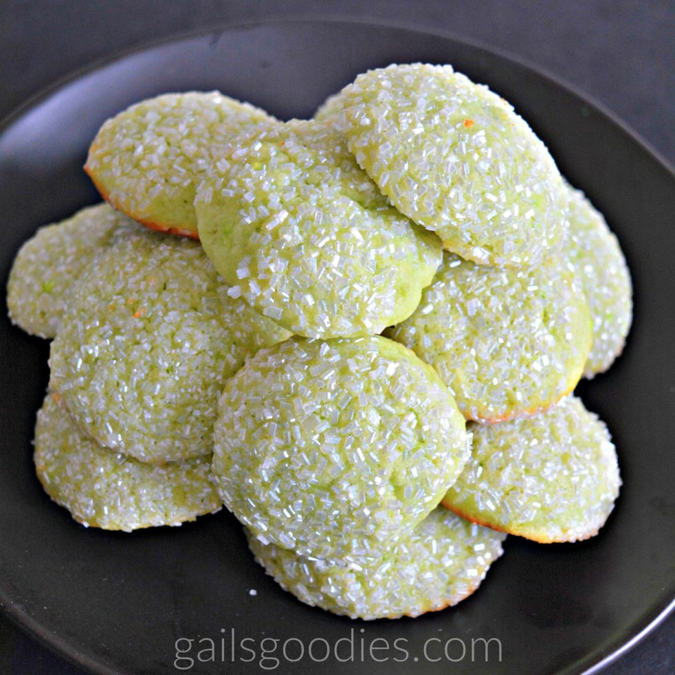 Small round lime green cookies are piled on a black plate. Each cookie is covered in sparkling white sugar crystals.