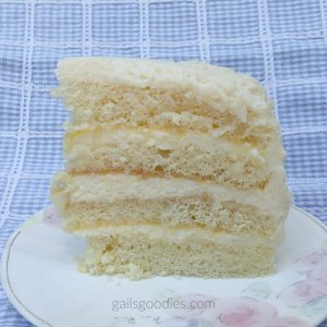 A slice of lemon mascarpone cake sits on a white plate with pale rose decorations. The point of the slice is on the left side and the view is a full side view so you can see the layers. There are four layers of light white sponge cake. In between each layer is a layer of mascarpone frosting and a very thin layer of lemon curd. The top and sides of the slice are covered in lemon mascarpone frosting.