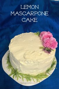 A whole cake sits on a white plate with a vibrant blue background. The cake is about 6 inches tall and is covered with creamy white frosting. There is a ring of light green lavender leaves around the base of the cake. Three pink roses, two lavender flowers and a few lavender leaves are arranged in an arc on the top of the cake on right side. The words Lemon Mascarpone Cake are at the top of the photo