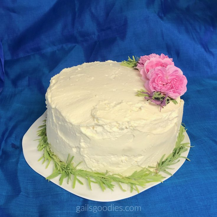 A whole cake sits on a white plate with a vibrant blue background. The cake is about 6 inches tall and is covered with creamy white frosting. There is a ring of light green lavender leaves around the base of the cake. Three pink roses, two lavender flowers and a few lavender leaves are arranged in an arc on the top of the cake on right side.