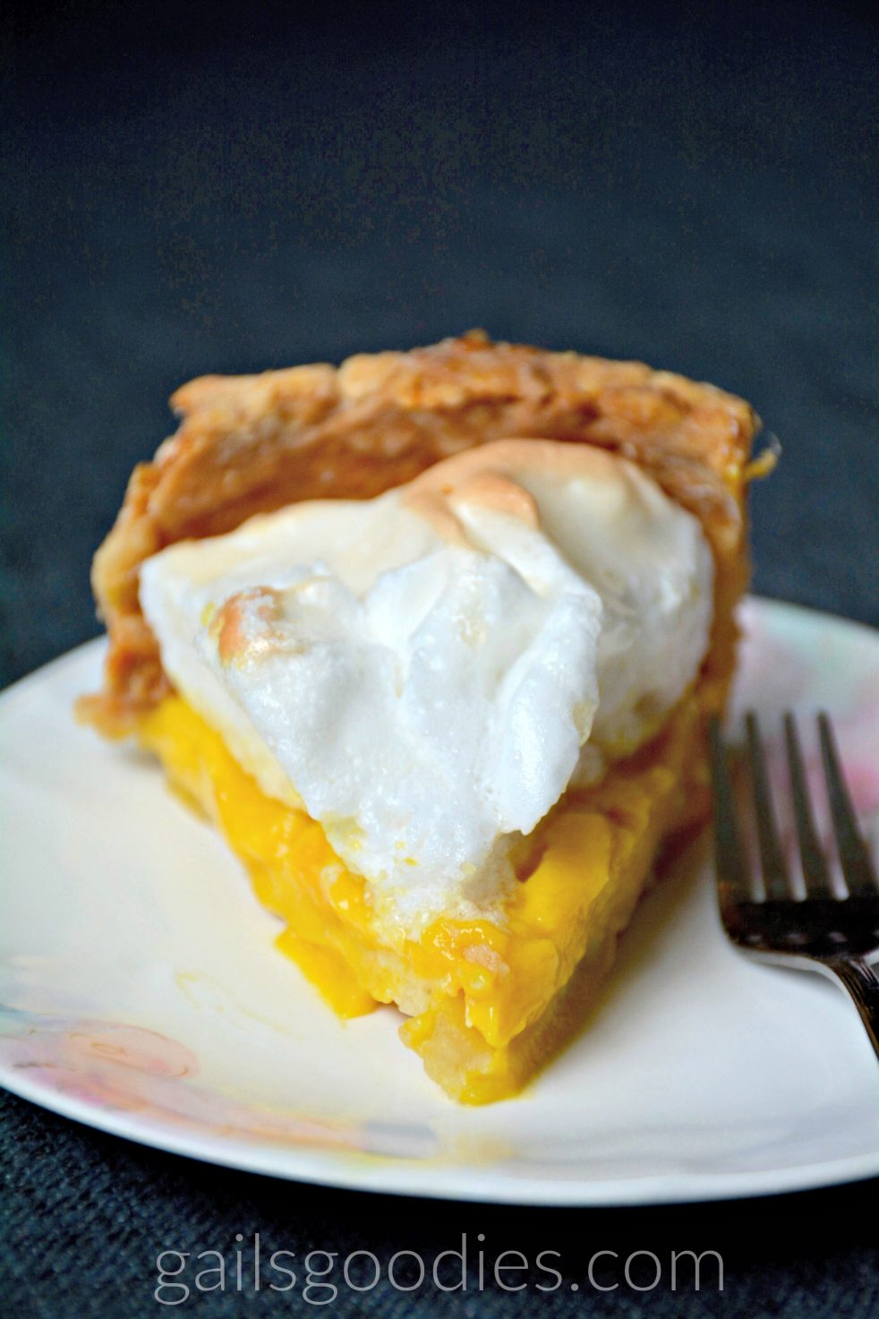 A slice of mango meringue pie sits facing directly forward on a plate. The bottom layer of bright orange mango curd is topped with mounds of golden meringue.